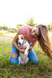 Cute girl is playing with her dog in the park. Young pet dog breeds beagle walking in park outdoors. woman carefully walks puppy, plays and trains, sits with pet royalty free stock photography