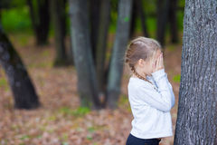 Cute girl playing hide and seek near tree in Stock Photos