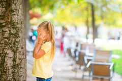 Cute girl playing hide and seek near tree in Paris. Little girl playing hide and seek in park outdoors Royalty Free Stock Photo