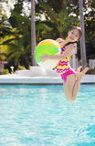 Cute Girl playing and jumping in the swimming pool Stock Photo
