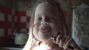 Cute girl playing with loupe stock video