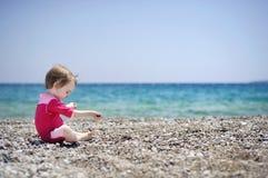 Free Cute Girl Playing On Pebble Beach Stock Image - 14253471