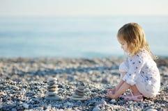 Free Cute Girl Playing On Pebble Beach Stock Photo - 29990070