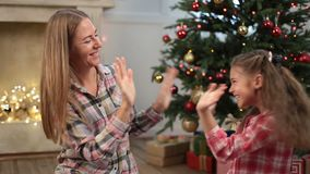 Cute girl playing pat-a-cake with mom on Xmas eve stock video footage