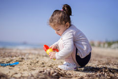 Cute girl playing with the sand on a beach Stock Photography