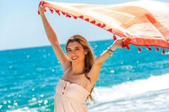 Cute girl playing with scarf on beach. Royalty Free Stock Photo