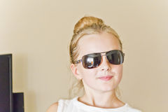 Cute girl playing with sunglasses Stock Image