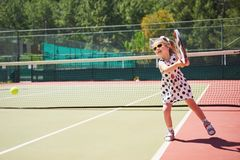 Cute girl playing tennis and posing for the camera.  Royalty Free Stock Images