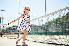 Cute girl playing tennis and posing for the camera.  Stock Image