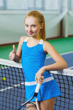 Cute girl playing tennis and posing or show thumb up  in court indoor Royalty Free Stock Photography