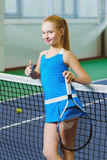 Cute girl playing tennis and posing or show thumb up  in court indoor Royalty Free Stock Image