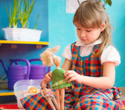 Cute girl playing with toy doll at kindergarten Stock Image