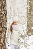 Cute girl playing in a winter forest. Royalty Free Stock Photography