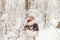 Cute girl playing in a winter forest. Stock Photography