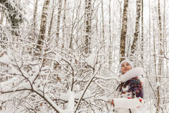 Cute girl playing in a winter forest. Royalty Free Stock Images