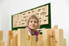 Girl  collecting   wooden puzzle. Cute  girl playing with wooden puzzles royalty free stock photography