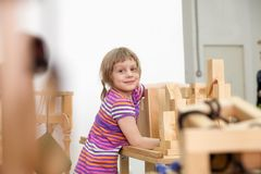 Cute girl playing in wooden puzzles. Girl of 5 years collecting wooden puzzle in playroom royalty free stock photography