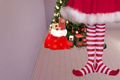 Cute girl with pointed elven feet wearing elf legging standing in a room with a christmas tree and santa claus bag full of stock illustration