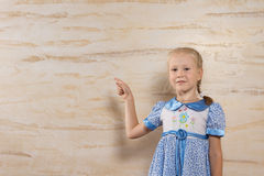 Cute girl pointing to the wooden wall behind her Stock Photos