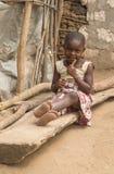 Pokomo girl sitting on log in Kenya, Africa. A cute girl of the Pokomo tribe in Kenya, Africa, sits on a log at Ngao village, Tana river County Royalty Free Stock Image