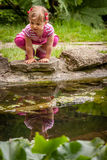 Cute girl by the pond Stock Photos