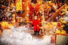 Cute girl on the porch. Pretty three year old girl is sitting near his house decorated for Christmas in a deer suit with horns on the head. Merry Christmas and stock photography
