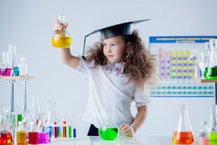 Cute girl posing with colorful test-tubes in lab Stock Photo