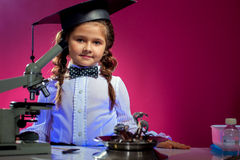 Cute girl posing in graduate hat, on pink backdrop Royalty Free Stock Images