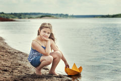 Cute girl posing with homemade paper boat by lake Stock Photography