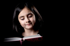 Cute girl posing while reading Stock Photography