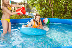 Cute girl pouring water over her friend in pool Royalty Free Stock Image