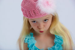 Cute girl pouting. Cute girl wearing a pink hat with feathers pouting Stock Photo