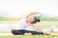 Cute girl practicing yoga pose on a mat in park Royalty Free Stock Photo
