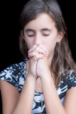 Cute girl praying with her eyes closed. (isolated on back Stock Photography