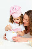 Cute girl preparing a cake with her mother. In the kitchen stock image