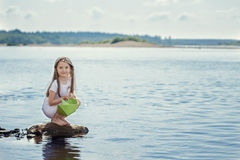 Cute girl preparing to launch paper boat at lake Stock Photo