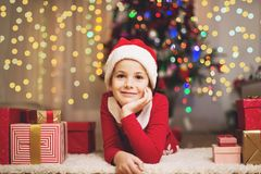 Cute girl with presents and Santa's hat on a Christmas/New Year's. Cute girl with presents and Santa's hat on a Christmas/New Year's Eve Royalty Free Stock Images