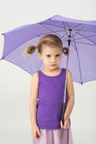 A cute girl in a purple clothes with umbrella Stock Photos