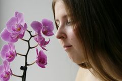 Cute girl with a purple orchid Royalty Free Stock Photography