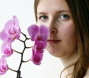 Cute girl with a purple orchid Royalty Free Stock Image