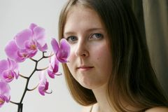 Cute girl with a purple orchid Royalty Free Stock Photo