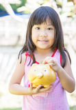 Cute girl put coin to piggy bank. Stock Photo