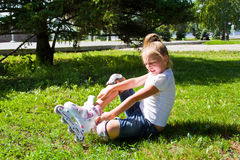 Cute girl put on roller skates Stock Photography
