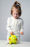 Cute girl putting her savings to a piggy bank Stock Photos