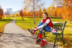 Cute girl putting on roller blades Royalty Free Stock Images