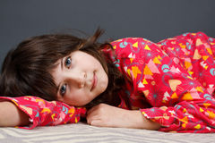 Cute girl in pyjamas. A cute 9-year-old girl lying in colourful pyjamas, looking into camera - grey background Stock Photography