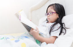 Cute girl reading book on bed Stock Photos