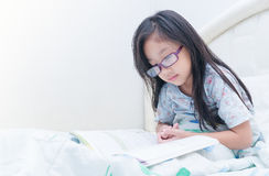 Cute girl reading book on bed Royalty Free Stock Images