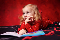 Cute girl reading a book on the bed Stock Images