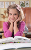 Cute girl reading book in classroom at school Stock Images